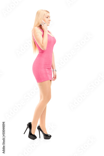 Full length portrait of an attractive woman talking on a phone