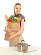 Woman in apron holding grocery bag