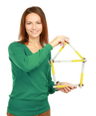 Woman holding a ruler in the form of a house