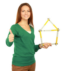 Woman holding a ruler in the form of a house and showing ok