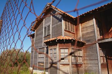 Fachada de una casa de madera tras una alambrada