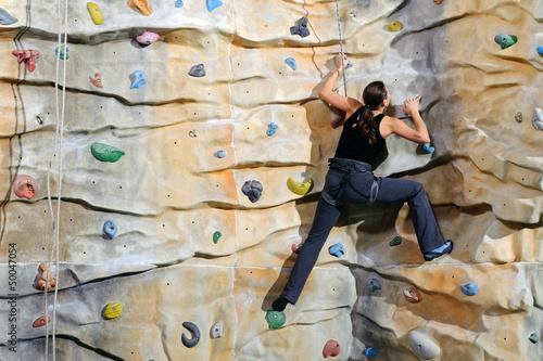 woman on rock wall in sport centre