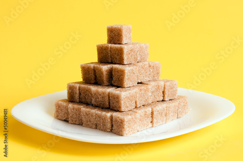 Unrefined sugar on a yellow background