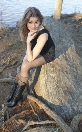Model relaxing on a rock by a lake