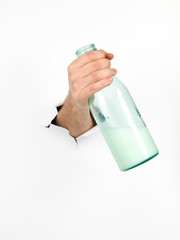 male hand holding a glass bottle of milk