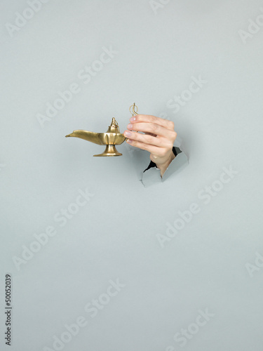 female hand holding magic lamp