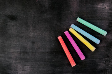 Row of color chalk on a blackboard