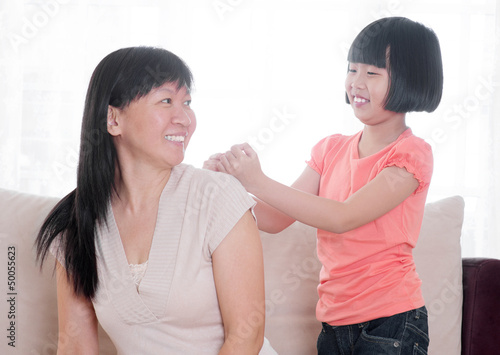 Asian child doing shoulder massage to her mother