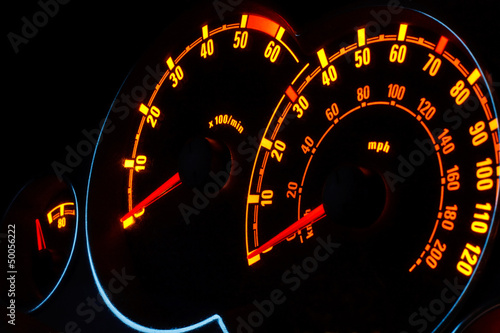 Backlit car dashboard dials glowing at night