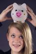 Teenie mit Zahnspange und Sparschwein auf dem Kopf