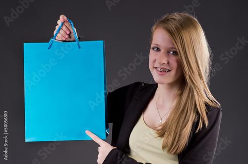 Blondes Mädchen zeigt auf blauen Shopping Bag
