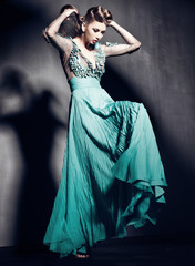 beautiful woman in green dress posing dramatic indoors
