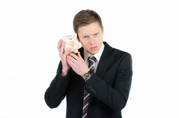 geschäftsmann hält sauer ein sparschwein ans ohr