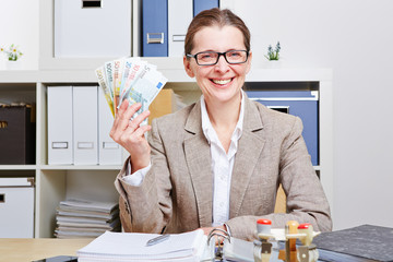 Frau im Büro mit Fächer aus Geldscheinen
