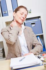 Frau mit Schmerzen im Nacken dehnt ihren Hals