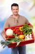 mann trägt eine kiste mit frischem gemüse