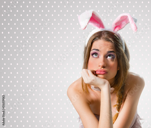 Woman with bunny ears thinking