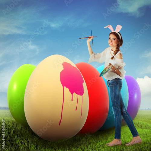 Woman coloring easter eggs on a field