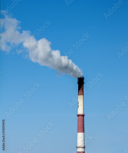 Industrial pipe with smoke on a blue sky background.