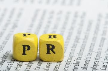 Word PR.Wooden cubes on magazine