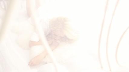 Sexy blonde girl in white bed, hidden behind veil