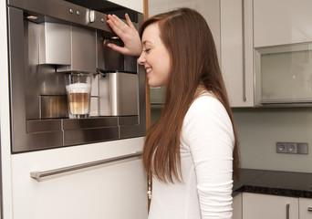 junge Frau mit Kaffeeautomat