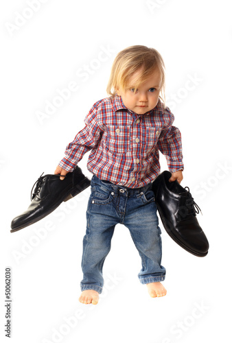 little girl has big shoes isolated on white background
