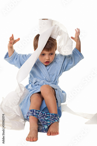 Little boy sitting on potty, rolls of toilet paper beside