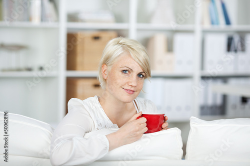 junge frau trinkt eine tasse kaffee auf dem sofa