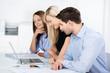 team im büro schaut auf laptop
