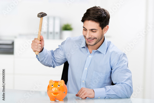 mann schlägt mit hammer auf sparschwein