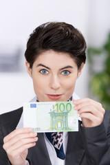 frau zeigt 100 euro geldschein