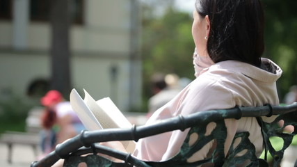 Pregnant woman resting in city park, reading a book