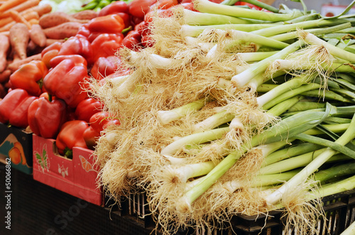 green onions and peppers on market stand