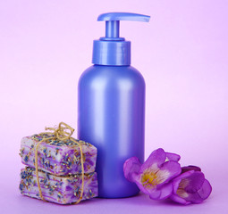 Liquid and hand-made soaps on purple background