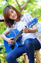 Beautiful asian woman holding blue Guitar