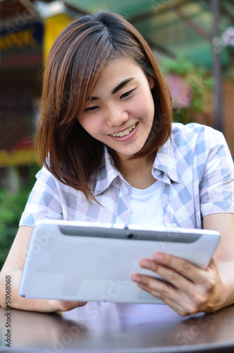Beautiful young student have good news on the tablet screen