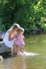 girl and her little daughter squirting water at the lake