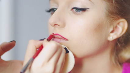 Professional makeup artist is applying lip gloss