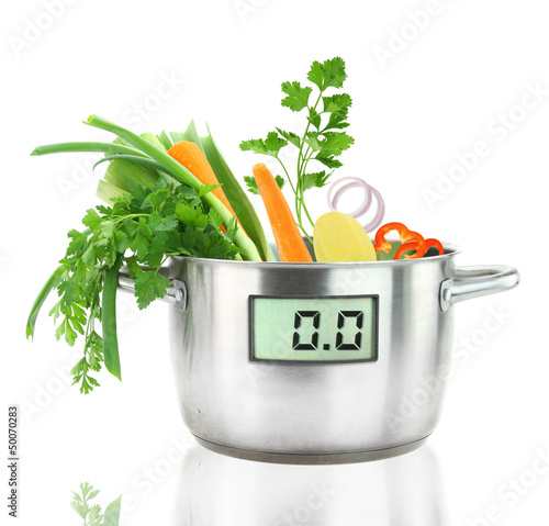 Fresh vegetables in a casserole pot with digital weight scale