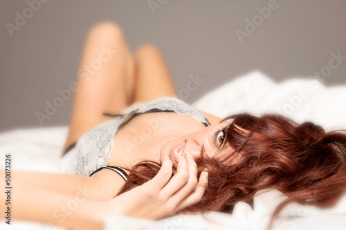 Woman in lingerie playing with her hairs in the bed