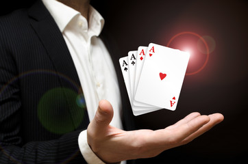 Man holding four poker aces