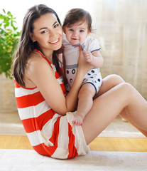 Happy smiling mother with baby girl indoor