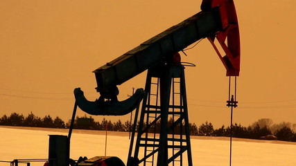 Oil production. Oil pumps at sunset Winter