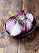 Halved red onions and thyme on a plate