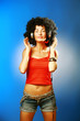 Beautiful woman with afro hair enjoying music with headphones .