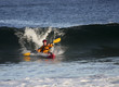 Kayak surfer escaping from big wave on rough sea