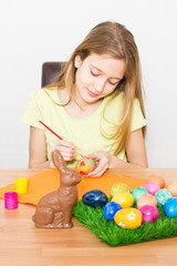 Beautiful young girl painting Easter eggs