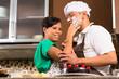 Asian couple baking chocolate cake in kitchen