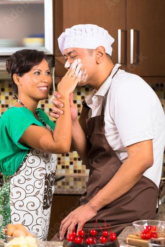 Asian couple baking chocolate cake in kitchen